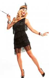 Black Dazzling Flapper dress with fringed one-shoulder dress, fishnets, pearls, headband, and a cigarette holder